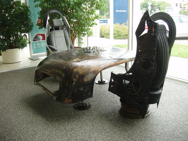 recycling material, burned Mercedes car and used tires to create this Design work of a chess table